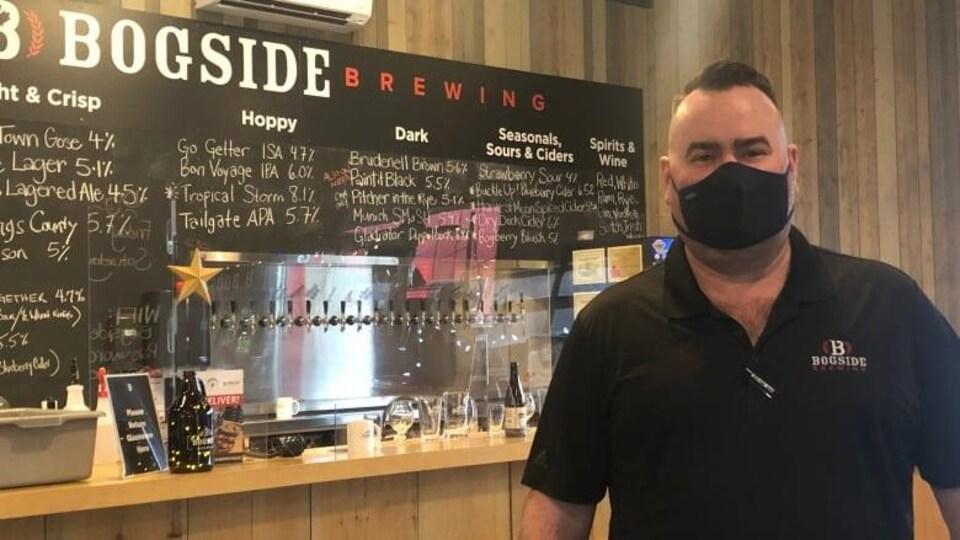 David McGuire pose pour la photo devant un comptoir de brasserie.