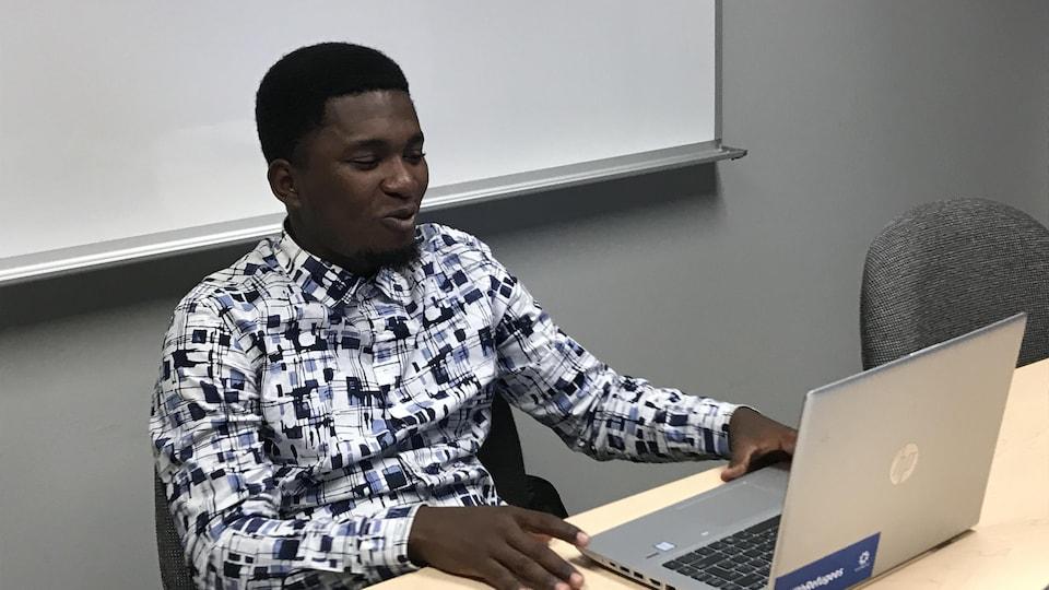 David Ndayizéyé assis devant un ordinateur dans une classe.