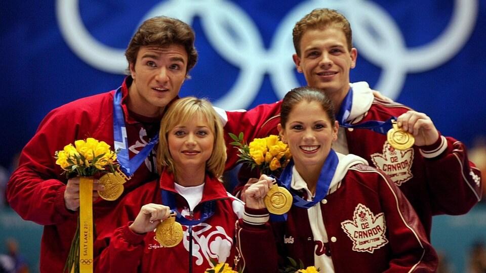 Les équipes canadienne et russe montrent leur médaille d'or.