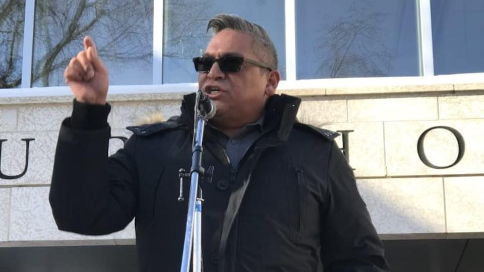 David Pratt parle dans un micro à l'extérieur d'un édifice.