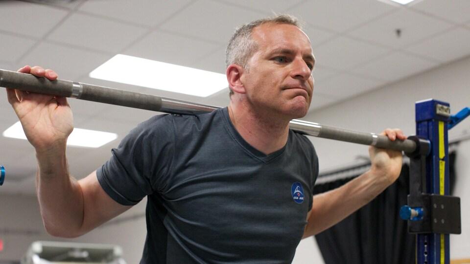 L'astronaute David Saint-Jacques soulevant des haltères dans le cadre de son entraînement.