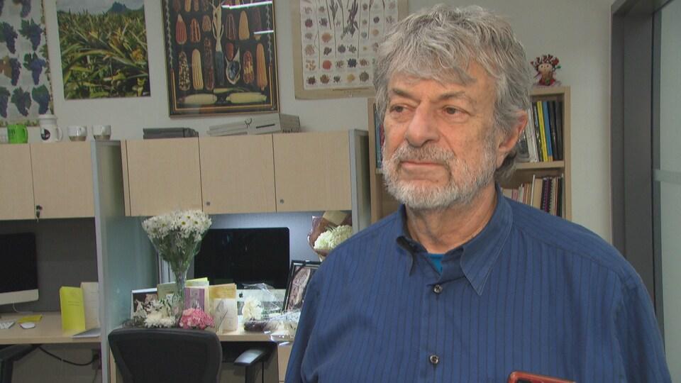 David Sankoff répond aux questions d'un journaliste près d'un bureau décoré de fleurs et de cartes de souhaits.