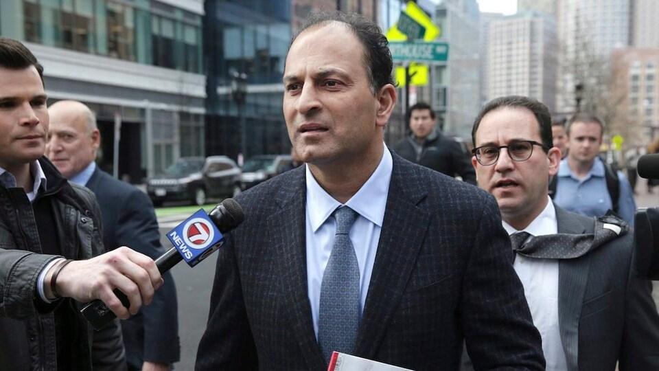 Un homme en veston fait face à des journalistes. Un homme le suit, la cravate au vent.