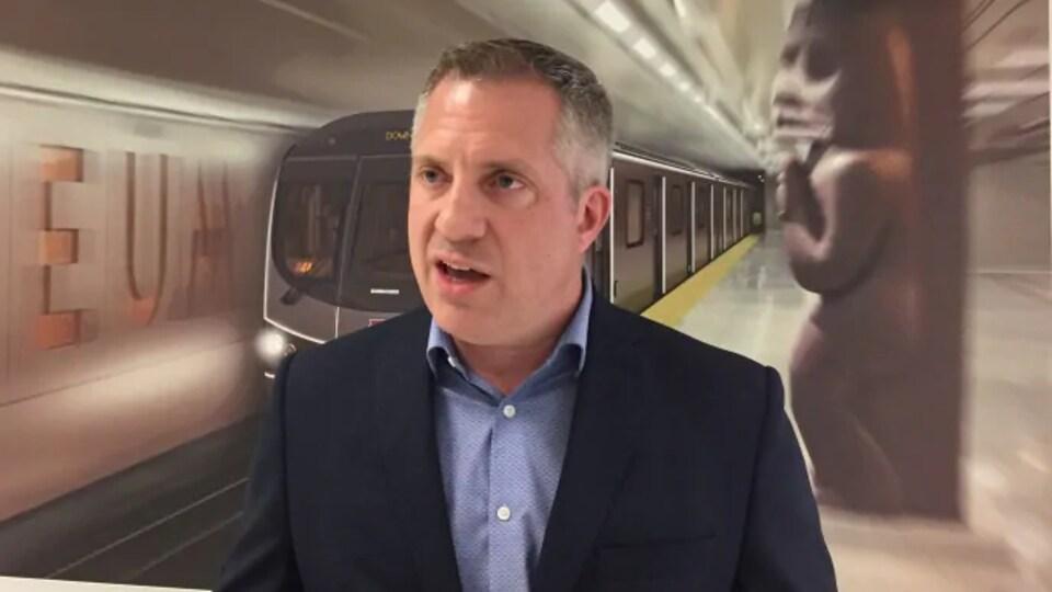 Un homme avec un métro derrière.