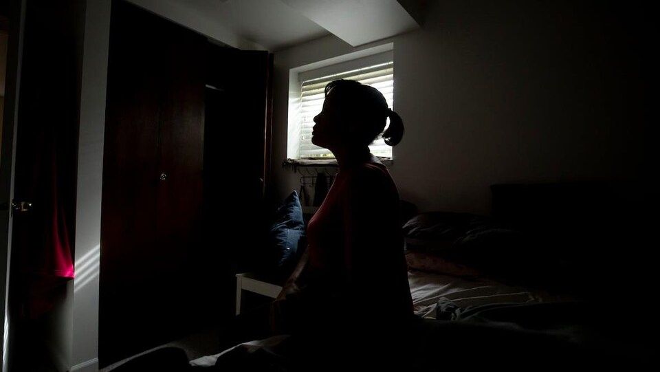 Une femme assise dans une chambre sombre.