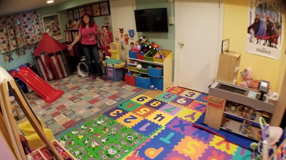 Une dame se tient au milieu d'une pièce de jeux pour enfants.