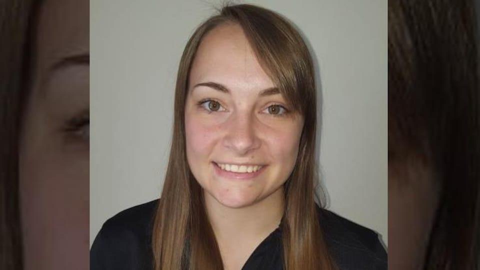 Une jeune femme habillée en noir. Elle a des cheveux bruns. Elle sourit.