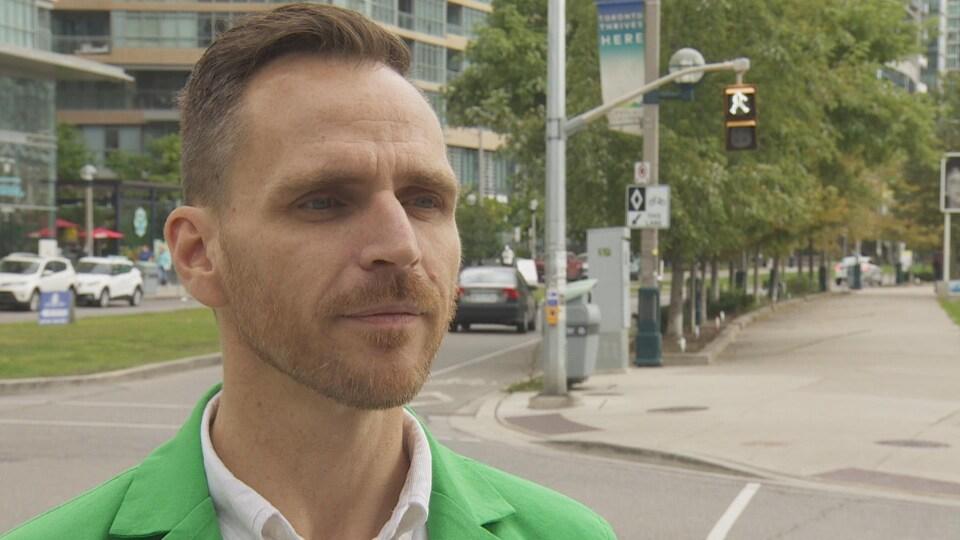 Un homme portant un chandail vert dans la rue.
