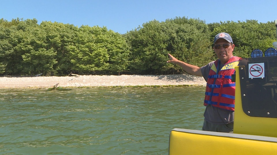 Un homme avec une ceinture de sauvetage sur un bateau pointe une île en expliquant des choses.
