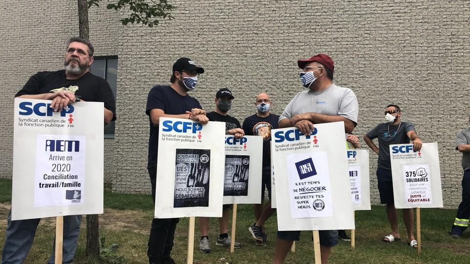 Des grévistes du SCFP tenant des pancartes appelant au respect de la conciliation travail-famille.