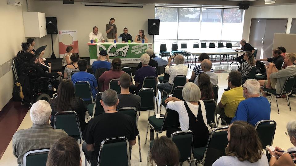 Les quatre candidats sont devant une table sur une scène, face à des dizaines de personnes. Isabelle Lévesque est debout et parle au micro.