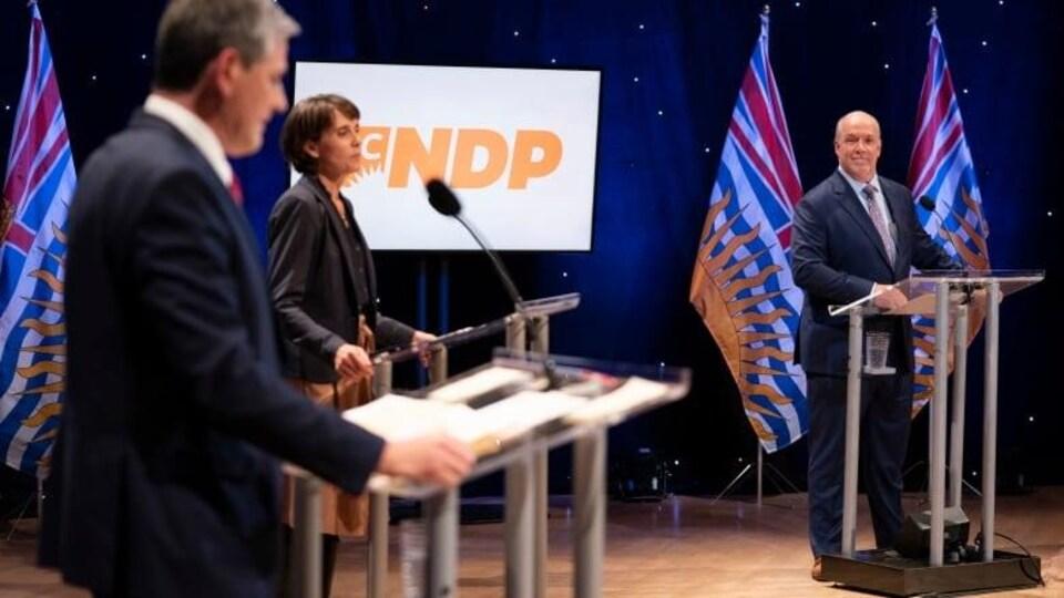 La chef des verts Sonia Furstenau est debout à un lutrin entre le chef libéral Andrew Wilkinson et le chef du NPD John Horgan.