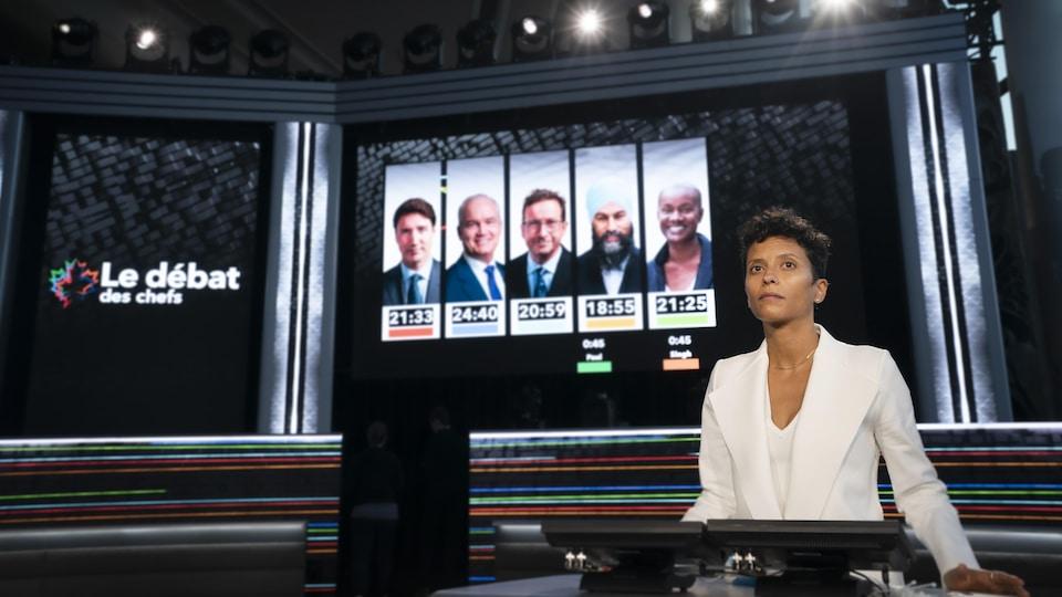 Noémi Mercier sur le plateau de télévision, avec une image des cinq chefs en arrière-plan.