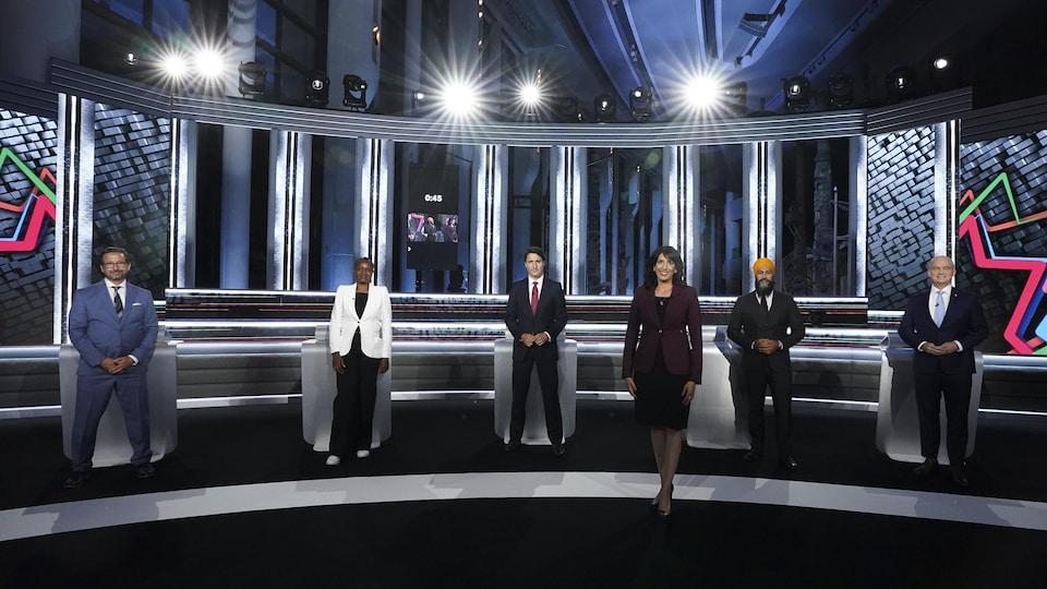 Shachi Kurl pose à l'avant-plan sur le plateau du débat, avec les chefs à l'arrière.