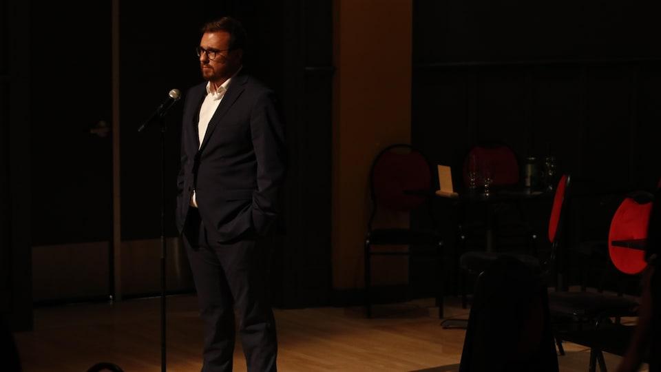 Mario Simard se tient derrière un micro dans une salle sombre.