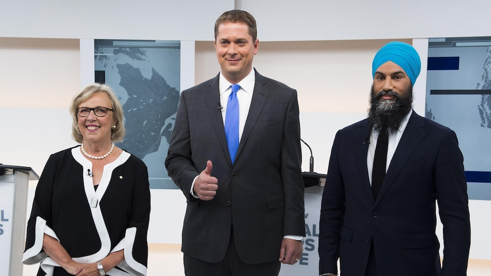 Elizabeth May, Andrew Scheer et Jagmeet Singh sourient à la caméra avant le débat.