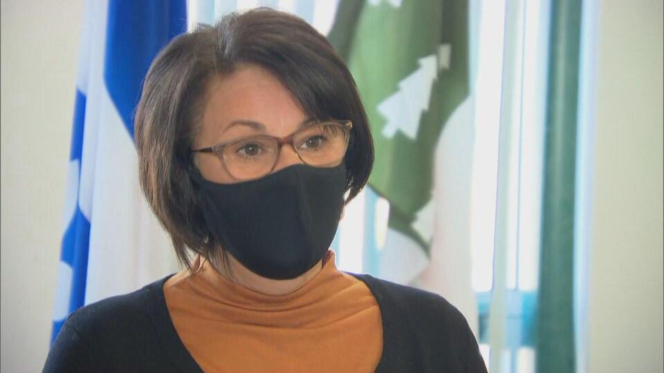 Une femme portant le masque accorde une entrevue à la caméra.