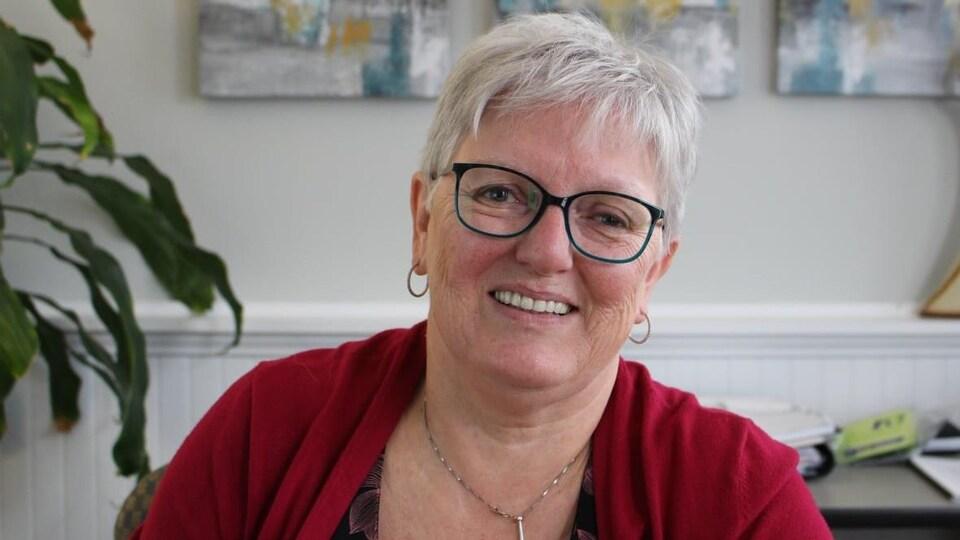 Debby Warren assise, sourit à la caméra.