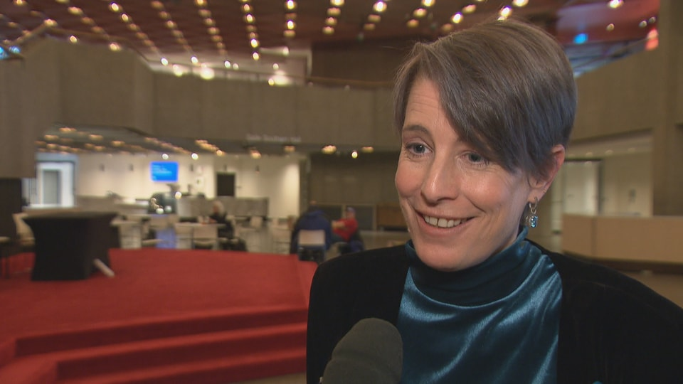 Debi Daviau répond aux questions d'une journaliste dans une grande salle.