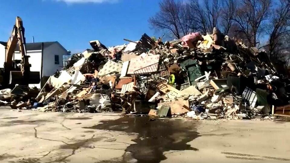 Une pelle mécanique empile des déchets de toutes sortes à Sainte-Marie, en Beauce.