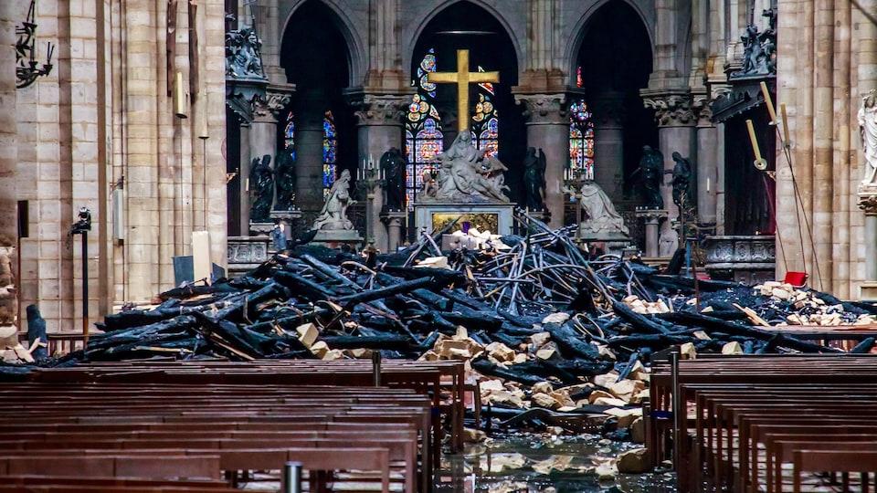 Plusieurs débris, dont des poutres en bois brûlées, reposent par terre après l'incendie qui a ravagé la cathédrale de Notre-Dame de Paris.