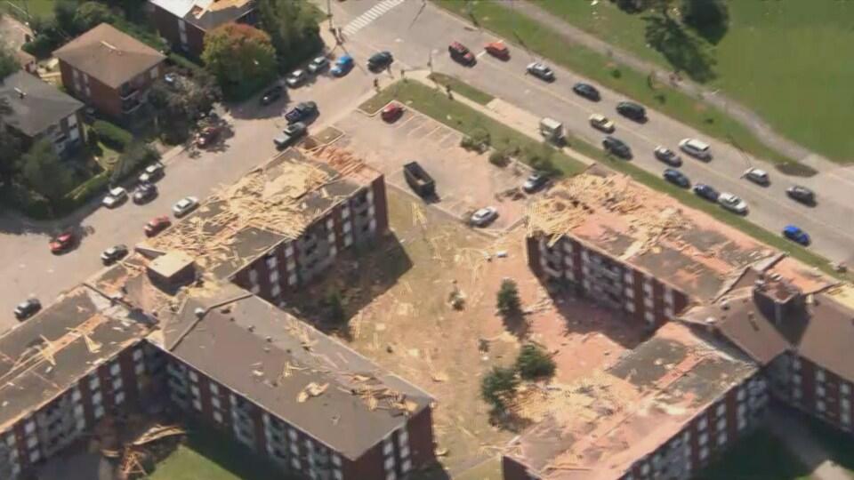 Des immeubles touchés par la tornade survenue vendredi. Les toits des édifices sont endommagés.