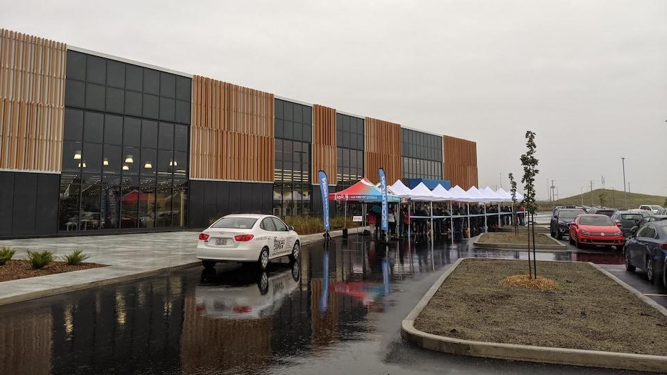 Un grand magasin, Décathlon, vu de l'extérieur avec des gens qui font la file pour y entrer