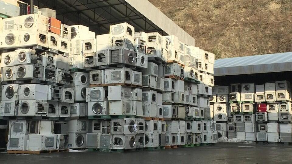 Pile de centaines de machines à laver le linge dans la cour d'une usine de recyclage