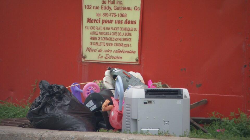 Des déchets près d'une boîte rouge de dons de la Saint-Vincent-de-Paul de Gatineau.