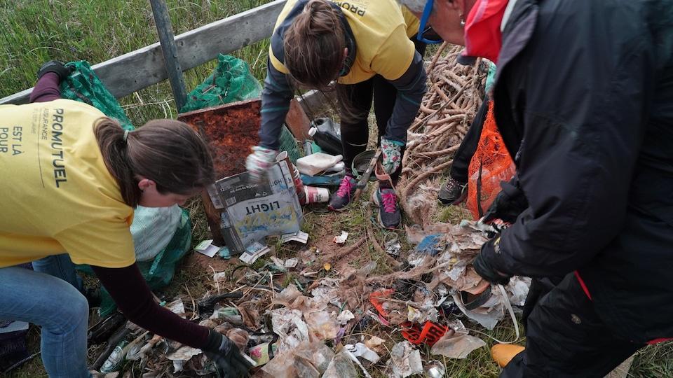 Des bénévoles se penchent pour récolter des déchets au sol.