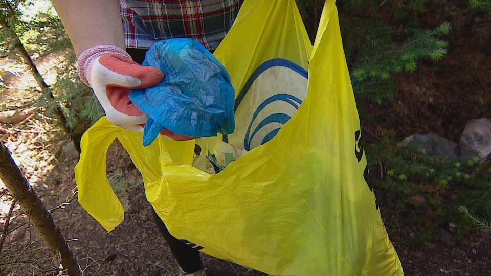 Une main tient un sac plastique qui a été retrouvé jeté par terre.
