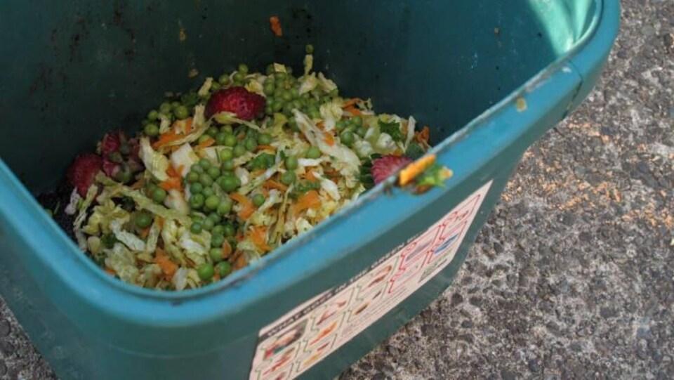 Une poubelle de compostage de déchets organiques avec de petits pois et d'autres légumes et fruits à l'intérieur.
