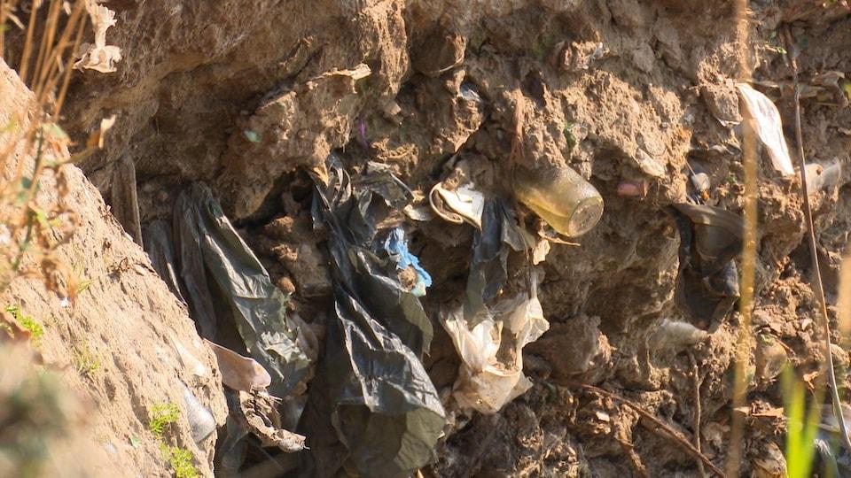 L'érosion du sol révèle de nombreux déchets tel que des bouteille de verre et des sacs de plastique qui ont été enfouis.