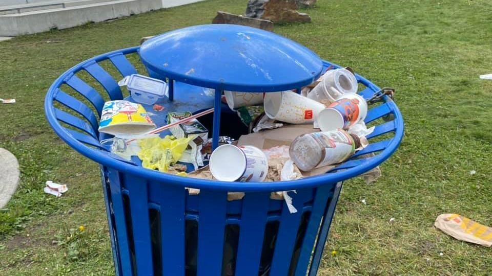 Une poubelle publique déborde de déchets.