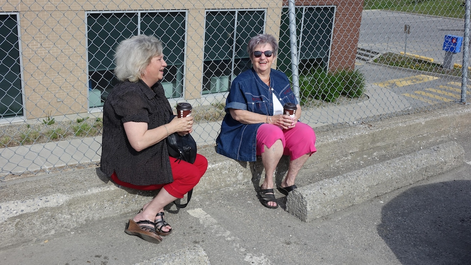 Deux femmes discutent, café à la main, dans un stationnement.