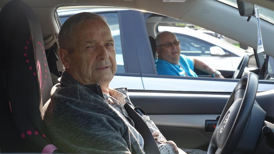 Deux hommes au volant de leur voiture.