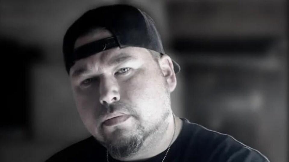 Un homme qui porte un t-shirt noir et une casquette noire.