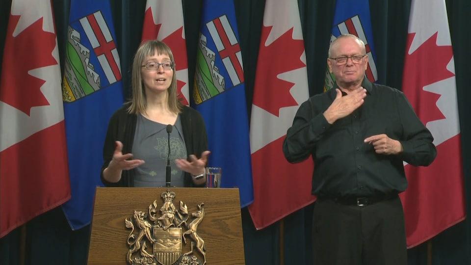 Deena Hinshaw parle au podium. L'interprète traduit en langue des signes.