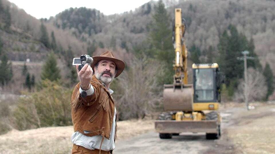 Un homme dans la nature tient une caméra devant lui. Il y a un camion derrière lui.