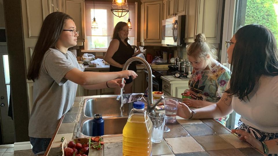Une femme se tient debout dans la cuisine. Au comptoir, une jeune fille se lave les mains. En face d'elle, deux jeunes femmes son assises côte-à-côte. Celle du centre est concentrée sur l'image affichée sur un téléphone cellulaire.