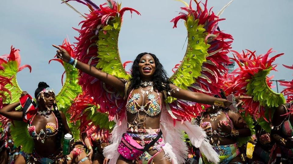 Une femme noire en tenue de carnaval de toutes les couleurs défile dans la rue avec d'autres danseuses à ses côtés.