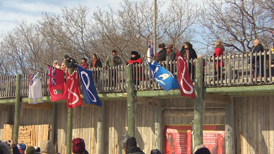 Des drapeaux métis sur une palissade d'un fort en bois.