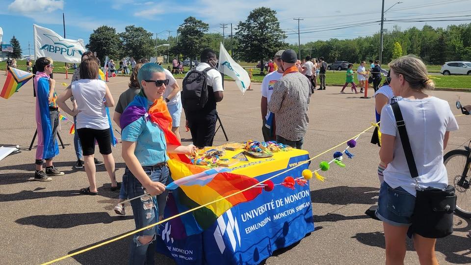 Des personnes portant des drapeaux et objets arc-en-ciel, rassemblées dans un stationnement sous le soleil.