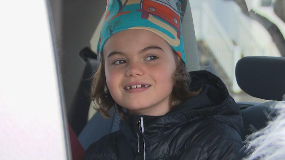 Petite fille souriante dans une voiture.