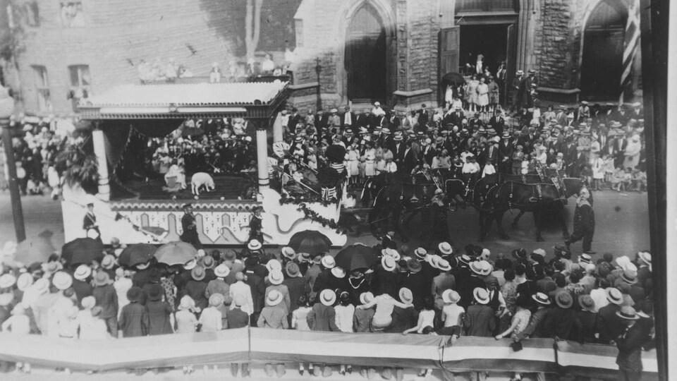 Un char allégorique défile devant de nombreux spectateurs.
