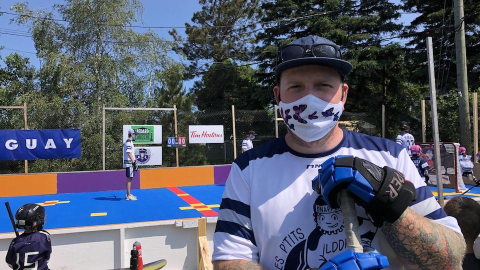Un homme porte un uniforme de hockey et porte son couvre-visage.