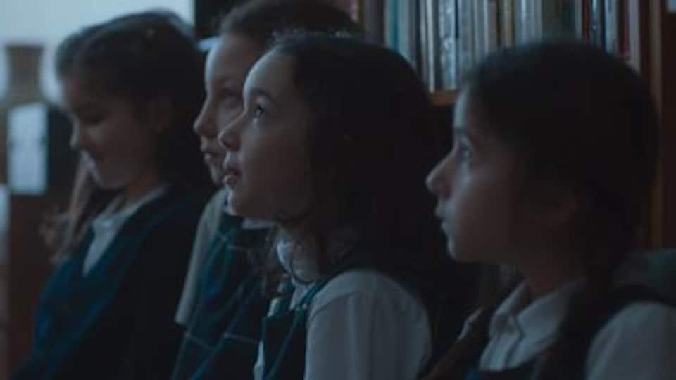 Quatre petites filles en uniforme scolaire.