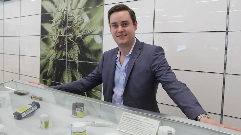 John Arbuthnot est devant un comptoir de magasin et sourit. Une grande image de fleurs et de  feuilles de cannabis est affichée au mur derrière lui.
