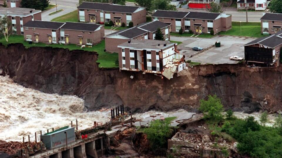 Des immeubles près d'un rivière qui a grugé les terrains qui la borde.