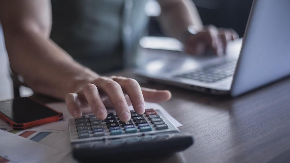 Un homme utilise une calculatrice et un ordinateur portable.
